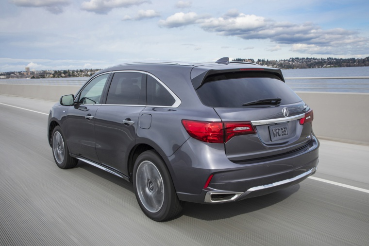 Picture of a driving 2019 Acura MDX Sport Hybrid in Modern Steel Metallic from a rear left perspective