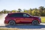 Picture of a driving 2019 Acura MDX A-Spec in Performance Red Pearl from a side perspective