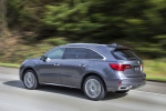 Picture of a driving 2019 Acura MDX Sport Hybrid in Modern Steel Metallic from a rear left three-quarter perspective