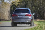 Picture of a driving 2019 Acura MDX Sport Hybrid in Modern Steel Metallic from a rear perspective