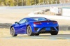 Driving 2018 Acura NSX Sport Hybrid SH-AWD in Nouvelle Blue Pearl from a rear left three-quarter view