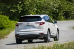 Picture of a driving 2020 Acura RDX SH-AWD in Platinum White Pearl from a rear right perspective