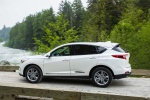 Picture of a driving 2020 Acura RDX SH-AWD in Platinum White Pearl from a rear left three-quarter perspective