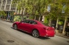 Driving 2018 Acura TLX Sedan in San Marino Red from a rear left three-quarter view