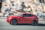 Picture of a driving 2019 Alfa Romeo Stelvio Quadrifoglio AWD in Rosso Competizione Tri-Coat from a left side perspective