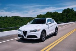 Picture of a driving 2019 Alfa Romeo Stelvio Ti Lusso AWD in Alfa White from a front left three-quarter perspective