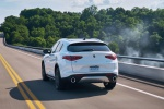 Picture of a driving 2019 Alfa Romeo Stelvio Ti Lusso AWD in Alfa White from a rear left perspective