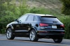 Driving 2017 Audi Q3 2.0T quattro in Brilliant Black from a rear left three-quarter view