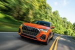 Picture of a driving 2020 Audi Q3 45 quattro in Pulse Orange from a front left perspective