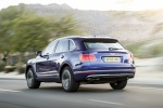 Picture of a driving 2019 Bentley Bentayga in Sequin Blue from a rear left three-quarter perspective