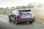 Picture of a driving 2019 Bentley Bentayga in Sequin Blue from a rear left perspective