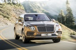 Picture of a driving 2019 Bentley Bentayga in Amber Metallic from a front right perspective