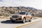 Picture of a driving 2019 Bentley Bentayga in Amber Metallic from a front left three-quarter perspective
