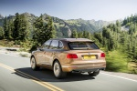 Picture of a driving 2019 Bentley Bentayga in Amber Metallic from a rear left three-quarter perspective