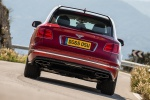 Picture of a driving 2019 Bentley Bentayga in Rubino Red Metallic from a rear perspective