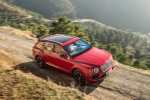 Picture of a driving 2019 Bentley Bentayga in Rubino Red Metallic from a front right three-quarter top perspective