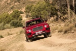 Picture of a driving 2019 Bentley Bentayga in Rubino Red Metallic from a frontal perspective