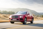 Picture of a driving 2019 Bentley Bentayga in Rubino Red Metallic from a front left three-quarter perspective