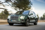 Picture of a driving 2019 Bentley Bentayga in British Racing Green 4 Metallic from a front left perspective