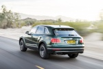 Picture of a driving 2019 Bentley Bentayga in British Racing Green 4 Metallic from a rear left three-quarter perspective