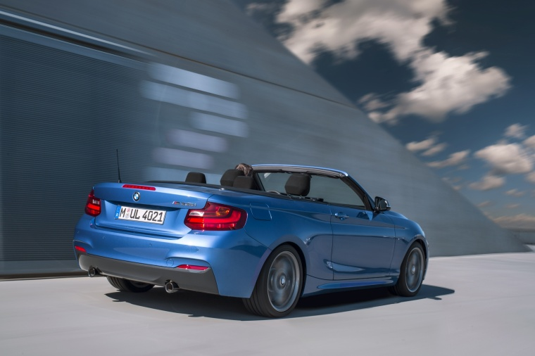 Driving 2017 BMW 2-Series M Convertible in Estoril Blue Metallic from a rear right three-quarter view