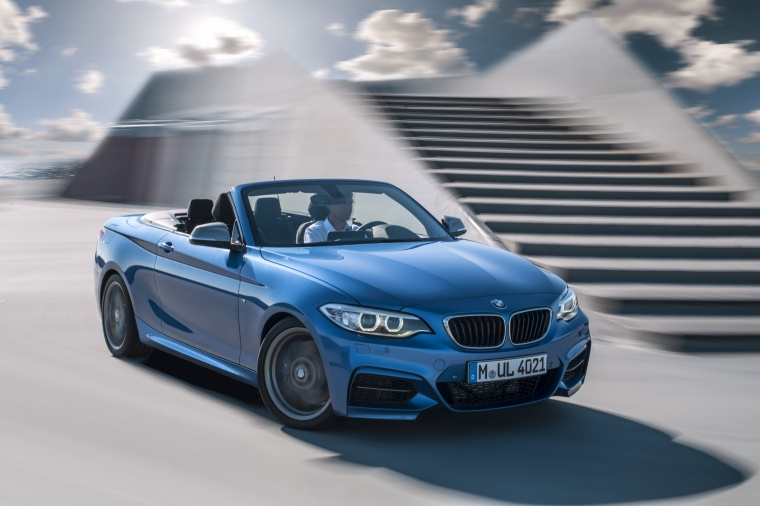 Driving 2017 BMW 2-Series M Convertible in Estoril Blue Metallic from a front right three-quarter view