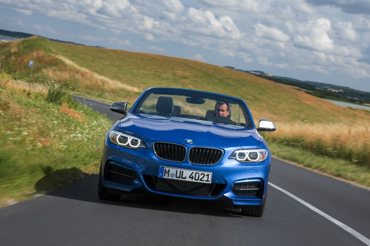 Driving 2017 BMW 2-Series M Convertible in Estoril Blue Metallic from a frontal view