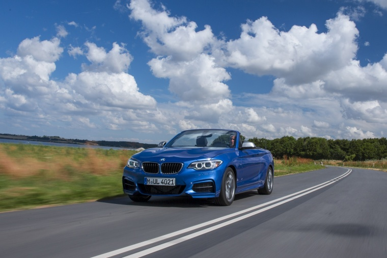 Driving 2017 BMW 2-Series M Convertible in Estoril Blue Metallic from a front left view