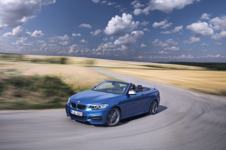 Driving 2017 BMW 2-Series M Convertible in Estoril Blue Metallic from a front left three-quarter view