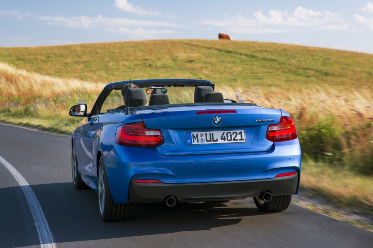Driving 2017 BMW 2-Series M Convertible in Estoril Blue Metallic from a rear left view