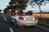 Driving 2017 BMW 2-Series Convertible in Glacier Silver Metallic from a rear left view