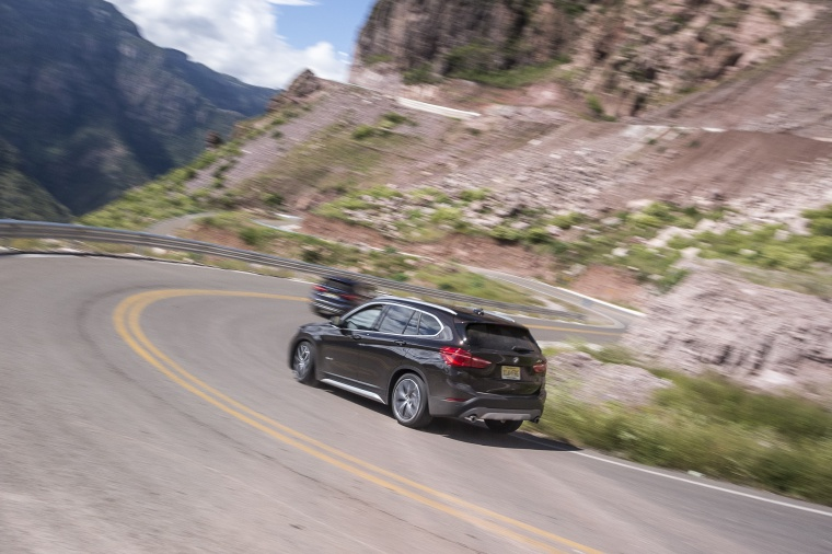 Picture of a driving 2019 BMW X1 xDrive28i in Jet Black from a rear left three-quarter perspective