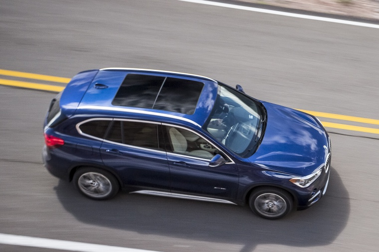 Picture of a driving 2019 BMW X1 xDrive28i in Mediterranean Blue from a front right three-quarter top perspective