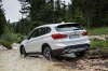 Picture of a driving 2019 BMW X1 xDrive28i in Alpine White from a rear left three-quarter perspective