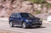 Picture of a driving 2019 BMW X1 xDrive28i in Mediterranean Blue from a front right three-quarter perspective