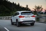 Picture of a driving 2019 BMW X1 xDrive28i in Alpine White from a rear left perspective