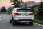 Picture of a driving 2019 BMW X1 xDrive28i in Alpine White from a rear perspective