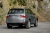 Driving 2010 BMW X3 xDrive30i in Space Gray Metallic from a rear right view