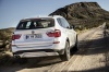 Driving 2017 BMW X3 in Mineral White Metallic from a rear right view