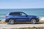 Picture of a driving 2018 BMW X3 M40i in Phytonic Blue Metallic from a right side perspective