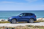 Picture of a driving 2018 BMW X3 M40i in Phytonic Blue Metallic from a left side perspective