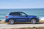 Picture of a driving 2019 BMW X3 M40i in Phytonic Blue Metallic from a right side perspective