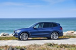 Picture of a driving 2019 BMW X3 M40i in Phytonic Blue Metallic from a left side perspective