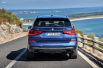 Picture of a driving 2019 BMW X3 M40i in Phytonic Blue Metallic from a rear perspective