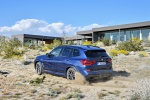 Picture of a driving 2019 BMW X3 M40i in Phytonic Blue Metallic from a rear left three-quarter perspective