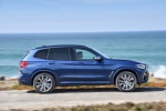 Picture of a driving 2020 BMW X3 M40i in Phytonic Blue Metallic from a right side perspective