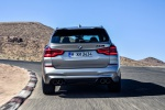 Picture of a driving 2020 BMW X3 M Competition in Donington Gray Metallic from a rear perspective