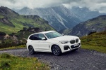 Picture of a driving 2020 BMW X3 xDrive30e PHEV AWD in Alpine White from a front right perspective