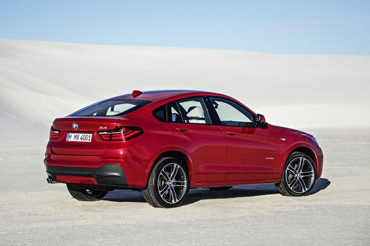 2017 BMW X4 in Melbourne Red Metallic from a rear right three-quarter view