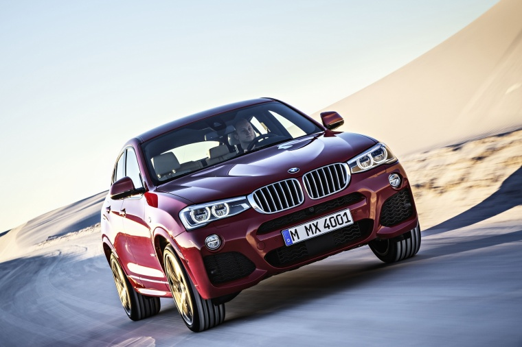 Driving 2017 BMW X4 in Melbourne Red Metallic from a front right view